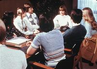 Students seated at a table listening to a faculty member in the College Center (now Christensen Center), circa 1976
