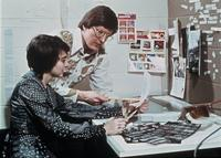 A faculty member and student review a document and photographic contact sheets in the College Center (now Christensen Center), circa 1976