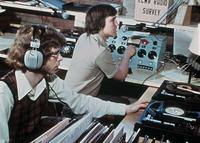 Two student disc jockeys operating the control booth of KCMR radio in Urness Tower, circa 1976