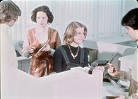 Four people working at a service desk, circa 1976