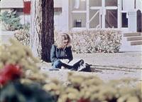 A student sitting on the ground in the Augsburg Quad, circa 1976