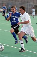 An Augsburg men's soccer player sprints forward in a game against St. Scholastica, 2003.