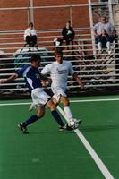An Augsburg men's soccer player defends an opponent, 2001.