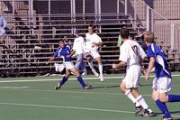 An Augsburg men's soccer player jumps up to defend, 2001.