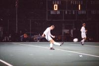 An Augsburg men's soccer player kicks the ball, 1996.