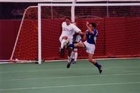 An Augsburg men's soccer player jumps in the tackle, 2001.
