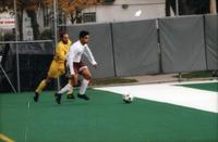 An Augsburg men's soccer player dribbles a defender, 1995.