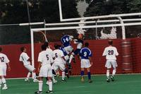The Augsburg men's soccer goalkeeper comes out to catch the ball, 2001.