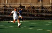 An Augsburg men's soccer player strikes the ball, 1999.