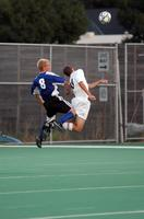 An Augsburg men's soccer player jumps up to head a ball in a game against St. Scholastica, 2003.