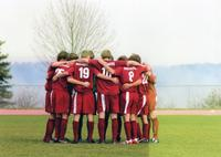Augsburg men's soccer players huddle together on the field, circa 2000.
