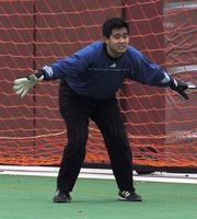 An Augsburg men's soccer goalkeeper gets ready to save a goal against Gustavus Adolphus, 2002.