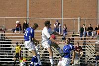 An Augsburg men's soccer player heads the ball, 2003.