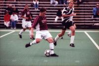 An Augsburg men's soccer player hits the ball, 2000.