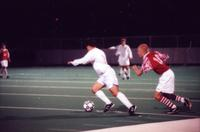 An Augsburg men's soccer player dribbles, 1996.