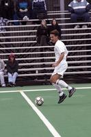 An Augsburg men's soccer player runs with the ball against Gustavus Adolphus, 2002.