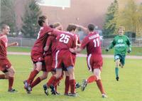 Augsburg men's soccer players celebrating together on the field, circa 2000.