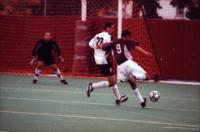 Gibran Lorenzano runs past a defender and shoots, 2000.