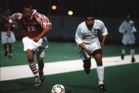 An Augsburg men's soccer player chases a ball, 1996.
