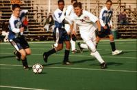 Auggie men's soccer Player runs forward with the ball, 1998.