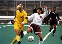 Augsburg men's soccer player attempts to take the ball from an opposing player at Edor Nelson field, circa 1995.