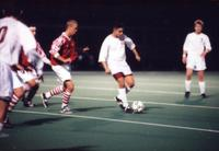 An Augsburg men's soccer player turns away with the ball, 1996.