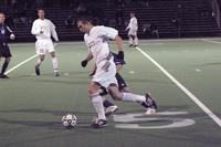 An Augsburg men's soccer player runs with the ball in a game against St. Thomas, 2003.