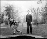 An Augsburg football player posing in Murphy Square while a young man stands next to him, 1926