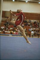 An Augsburg women's gymnastics team member performing a leaping arch, February 1976