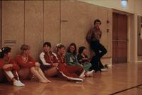 Augsburg women's gymnastics team seated near the walls conversing, circa 1976