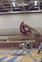 An Augsburg women's gymnastics team member doing a full arch on a balancing beam , February 1977