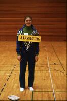 An Augsburg women's gymnastics team member posing for a photo with an Augsburg sign, February 1976