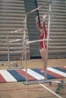 An Augsburg women's gymnastics team member in a stance in front of a high bar, February 1977