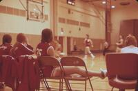 Three Augsburg women's basketball team players benched while the game proceeds, February 1976