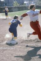An Augsburg women's softball team player running past a guarded base, circa 1976