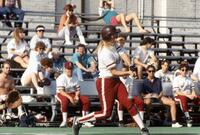 An Augsburg women's softball team player swinging a bat, May 1975