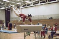 An Augsburg women's gymnastics team member doing a jumping hollow onto a hurdle, February 1977