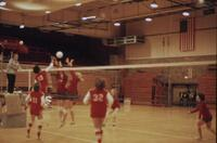Augsburg women's volleyball team players near the net serving the ball, November 1975