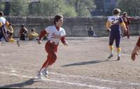 An Augsburg women's softball team player running as the rival team scrambles, circa 1976