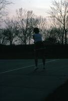 An Augsburg women's tennis team player jumping, circa 1975