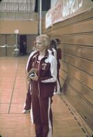 Augsburg women's gymnastics team standing near the bleachers, February 1977