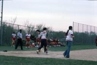 An Augsburg women's softball team player stepping onto a home base, April 1976