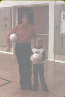 A woman and a little boy each with a volleyball, November 1976