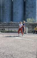 An Augsburg women's softball team player standing a base waiting for the hit, circa 1976