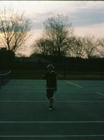 An Augsburg women's tennis team player walking on an outside court, circa 1976