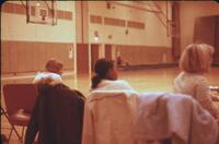 Three people seated watching an Augsburg Women's basketball game, February 1976