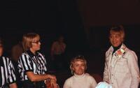 Referee conversing with two women, February 1975