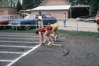 Augsburg women's track and field team runner standing at the starting mark for a race, April 1977