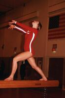 An Augsburg women's gymnastics team member lunging on a balancing beam, February 1975