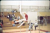 An Augsburg women's gymnastics team member on a low bar with her separated by the bar, February 1977